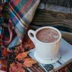 Mug of hot cocoa with blanket and book