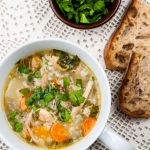 Vegetable soup in bowl with bread on table.
