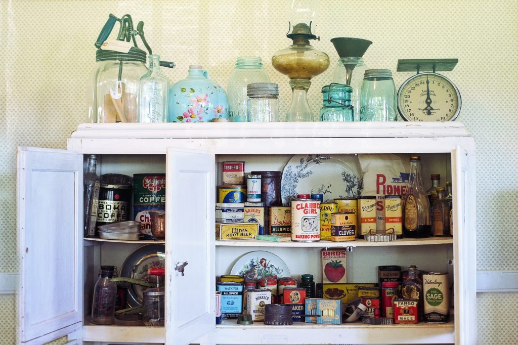 Cupboard with food items, antiques on top.