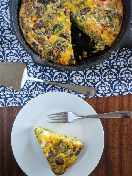 One slice of frittata on plate, the rest in cast iron pan.