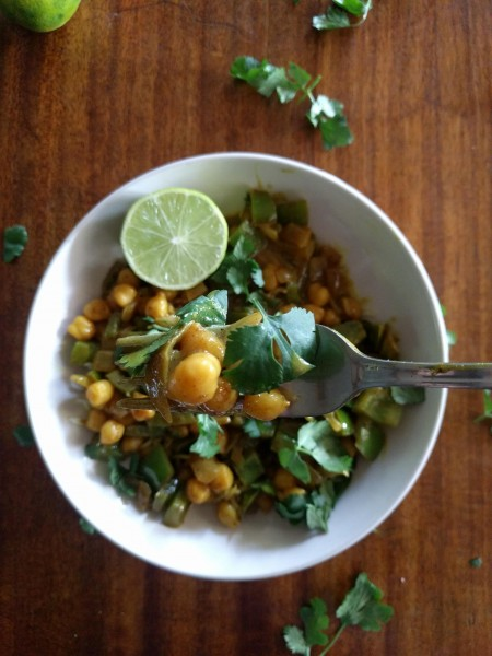 chickpea curry with cilantro on fork over bowl.