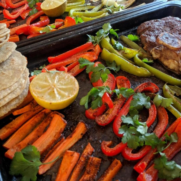 carrots, peppers, onion, and steak on a sheet pan.