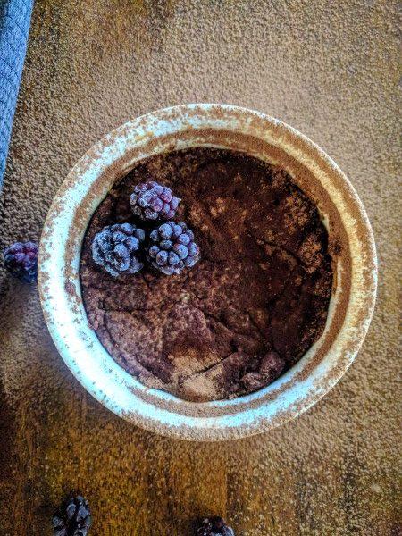 Personal brownie in ramekin. With blackberries on top.