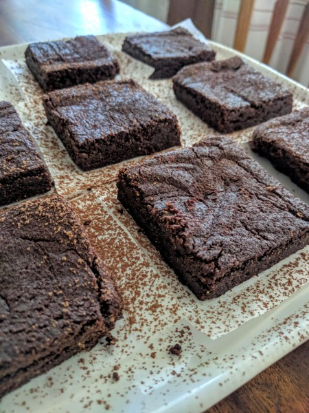 Finished brownies on a plate, dusted with cocoa powder.