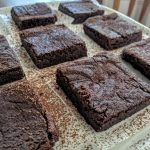 brownies on white plate, dusted with cocoa powder.