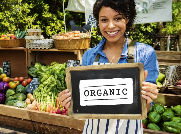Woman holding organic sign at farmer's market