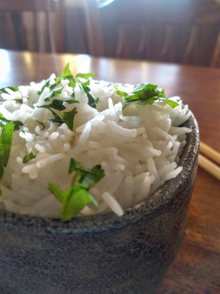 cooked rice in bowl, garnished with cilantro