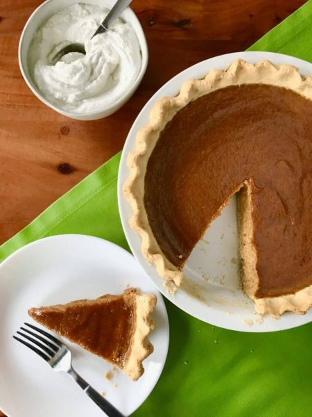 Pumpkin pie with slice on a plate