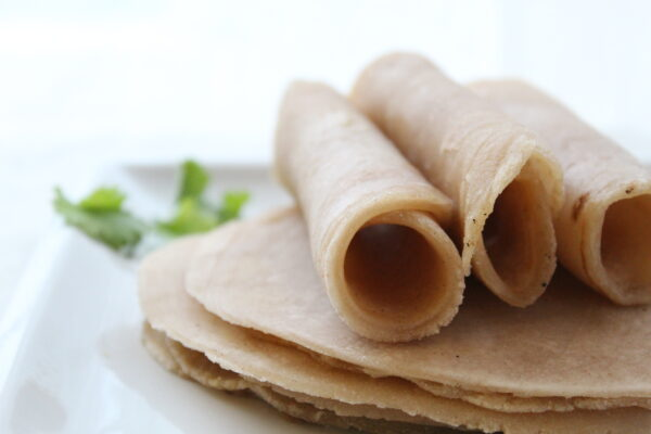 three rolled up tortillas on a white plate on a stack of more tortillas