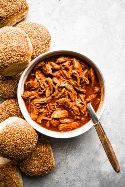 Pulled BBQ Chicken in a bowl next to Sesame Seed buns