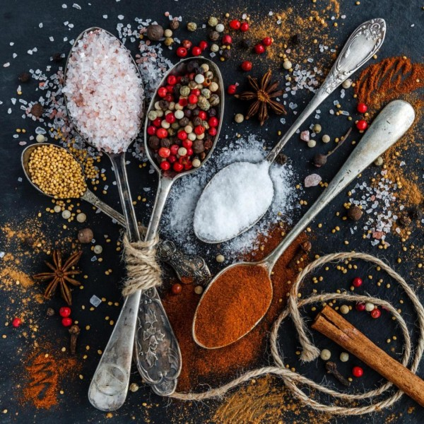 spices and spoons on a dark table
