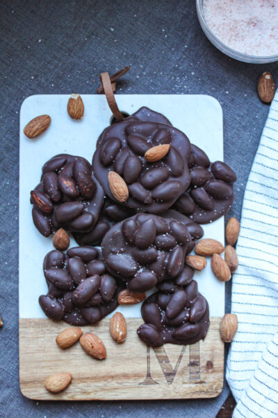 dark chocolate covered almond clusters on cutting board
