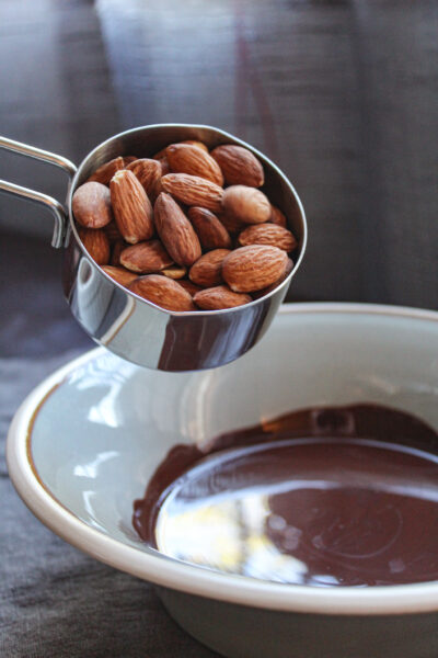 adding almonds to melted chocolate in bowl