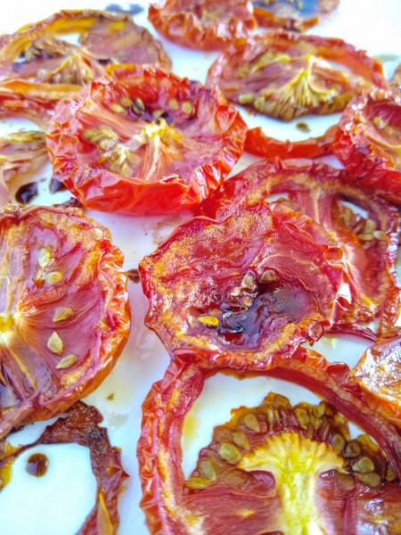 Oven roasted sliced tomatoes on white plate