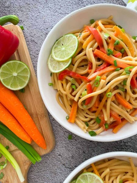 Thai noodles in a bowl with veggies on the side