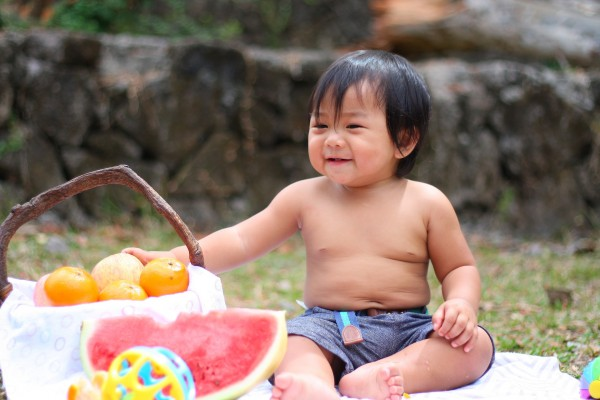 Happy kid eating healthy naturally sweet snack (fruit).
