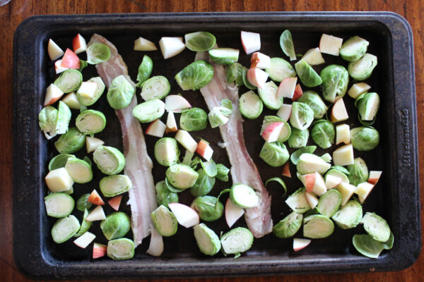 Apple bacon brussels sprouts on baking sheet ready to go in the oven.