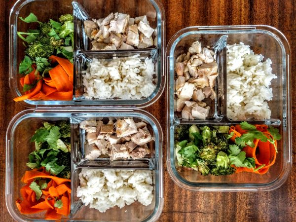Chicken, broccoli, carrot noodles and rice meal prep peanut sauce containers.