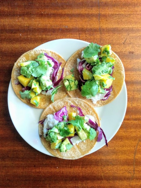 Overhead view of fish tacos with cabbage and avocado mango salsa.