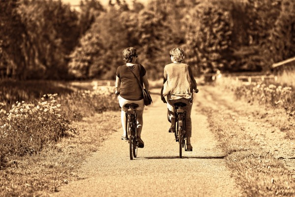 Two women riding a bike. Paleo is a lifestyle not just a diet.