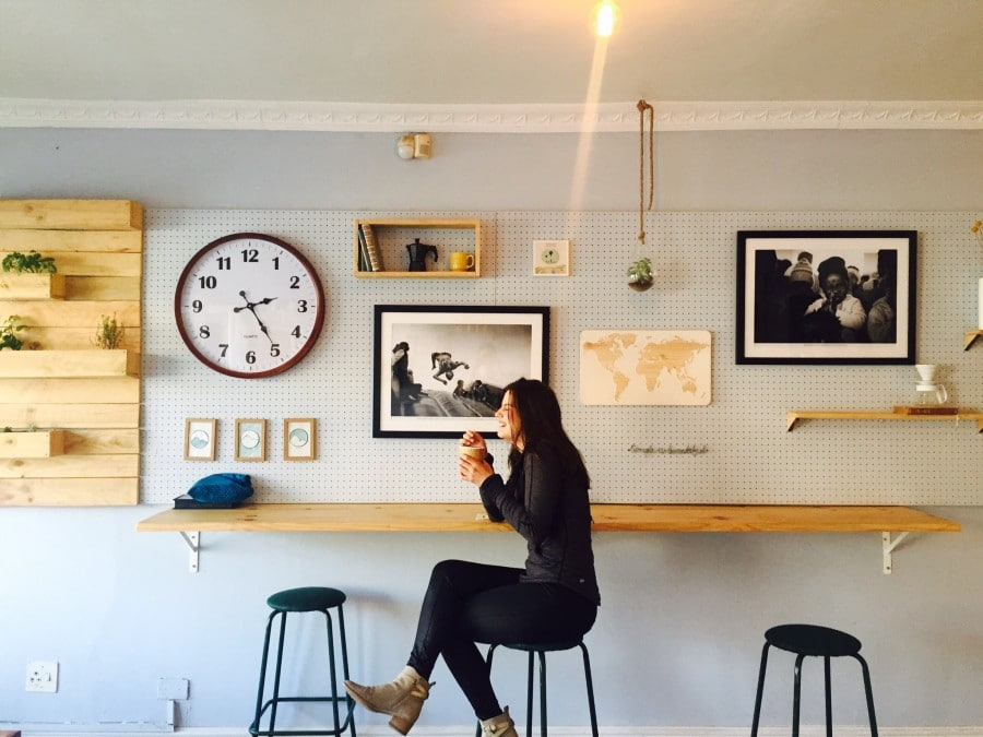Woman sitting with big clock on wall