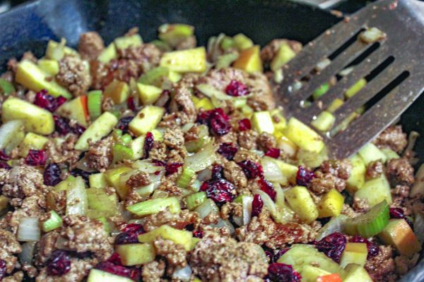 Stuffing ingredients - ground pork, onions, celery, apple and cranberries in the cast iron.