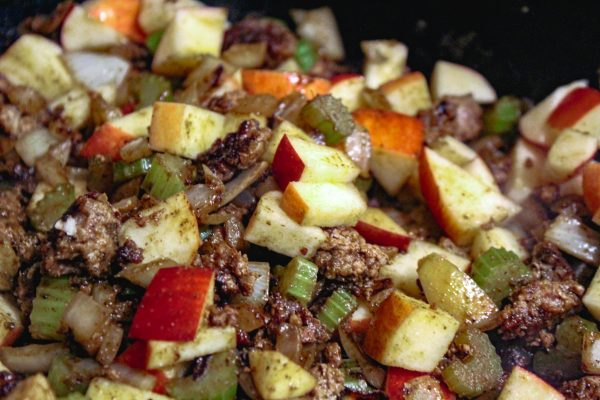 Add the apple next for the stuffing - in the cast iron.